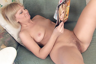 Sitting on the sofa, hairy mature Lana gets turned on reading a magazine. She can't help but to pull off all her clothes and finger fuck her blonde haired pussy!
